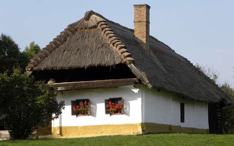 Falusi házikó, korabeli tetővel, virágokkal telített ablakok, megnyugtató környezet